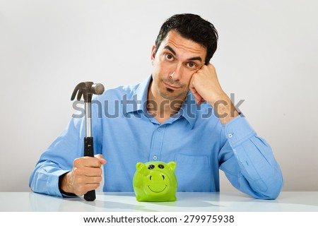 Indisposed young man with hammer in his hand hesitate whether to break piggy bank - stock photo
