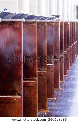Individual seats in the nave of a catholic church in a monastery - stock photo