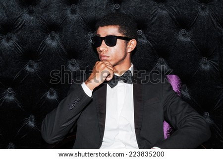 Individual style. Fashionable young Afro-American man sitting on the chair holding hand on chin  - stock photo