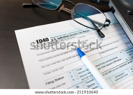 Individual tax return form 1040 on a table next to glasses, pen and laptop