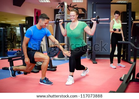 Individual training. Plus sized woman working out with personal trainer. Selective focus. - stock photo