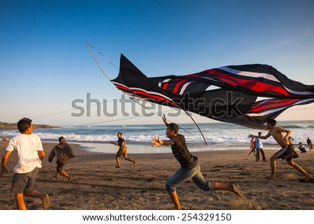 INDONESIA - AUGUST 17: Indonesian boys going to fly a kite near the coast AUGUST 17, 2014. During the Indonesian holidays, there are kite flying competitions which is a national tradition. - stock photo