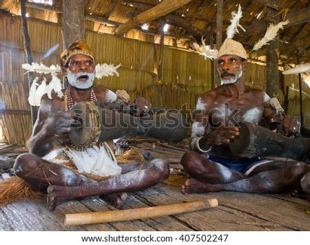 INDONESIA, IRIAN JAYA, ASMAT PROVINCE, JOW VILLAGE - JANUARY 19: Men Asmat tribe are sitting at home and play on the drum. On January 19, 2012  Jow Village, Asmat province, Indonesia