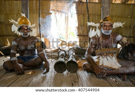 INDONESIA, IRIAN JAYA, ASMAT PROVINCE, JOW VILLAGE - JANUARY 19: Men Asmat tribe are sitting at home and play on the drum. On January 19, 2012  Jow Village, Asmat province, Indonesia - stock photo