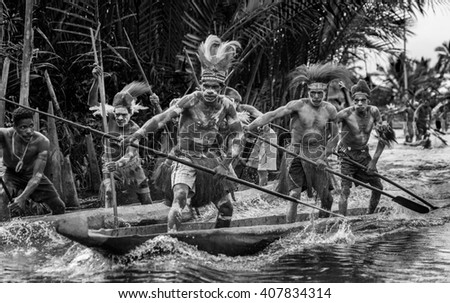 INDONESIA, IRIAN JAYA, ASMAT PROVINCE, JOW VILLAGE - JUNE 12: Warriors Asmat tribe are use traditional canoe. On June 12, 2012  Jow Village, Asmat province, Indonesia