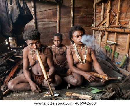 INDONESIA, ONNI VILLAGE, NEW GUINEA - JUNE 24: Korowai tribe Family sitting by the fire in a traditional house. Tribe of Korowai (Kombai).On June 24, 2012 in Onni Village, New Guinea, Indonesia