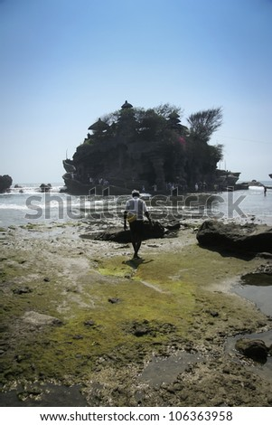 indonesian man walking towards the sea temple of tanah lot in bali indonesia - stock photo