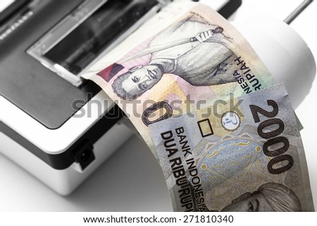 Indonesian rupiah money come out from calculator - stock photo