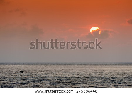 Indonesian Sunset. A small fishing boat, called a jukung, motors in the Banda Sea in the eastern part of the Indonesian archipelago during a beautiful sunset.