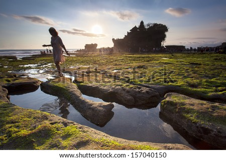 Indonesian temple in sea with tourist. Tanah lot complex. Bali. Indonesia - stock photo