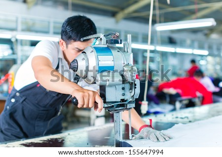 Indonesian worker using a cutter - a large machine for cutting fabrics - in a asian textile factory, he wears a chain glove - stock photo