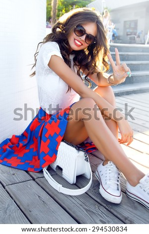 Indoor bright fashion summer portrait of stylish cheeky hipster woman, showing her tongue, have long brunette hairs perfect tanned fit slim body, wearing sneakers bikini pants and young sunglasses.