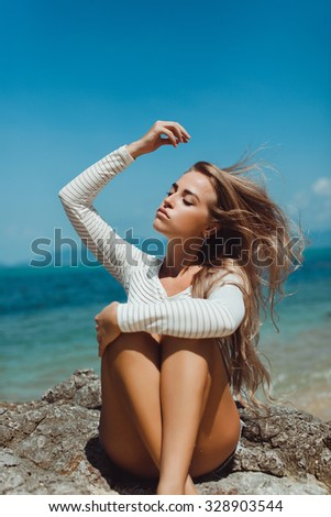 Indoor bright fashion summer portrait of stylish cheeky hipster woman, showing her tongue, have long brunette hairs perfect tanned fit slim body, wearing sneakers bikini pants and young sunglasses. - stock photo