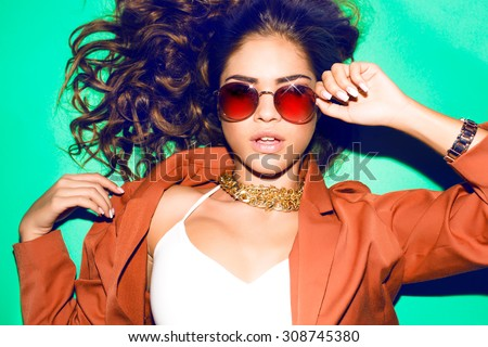 Indoor bright fashion summer portrait of stylish happy hipster woman,smoke make-up and having fun,have long brunette hairs perfect tanned fit slim body, wearing crop top and round sunglasses.Laying - stock photo