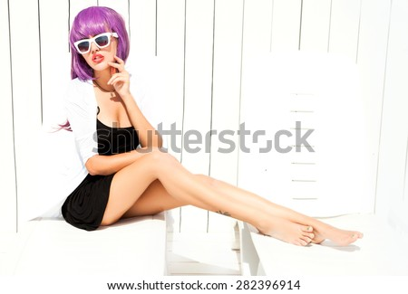 Indoor bright fashion summer portrait of stylish  hipster woman, showing her tongue, have long legs and cool bright wig,wearing sneakers bikini pants and young sunglasses. - stock photo