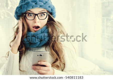 big glasses frames trend tizx  Indoor close up portrait of young beautiful surprising girl looking at  camera and holding smartphone