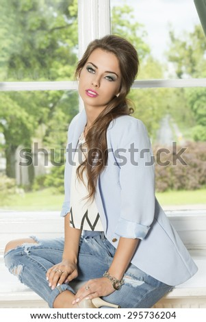 indoor fashion shoot of cute brunette girl with casual trendy clothes, elegant hair-style and stylish make-up sitting near window on green garden. Wearing jacket and jeans  - stock photo