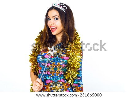 Indoor fashion studio portrait of beautiful smiling young party girl wearing bright sexy cocktail dress, funny crown and gold tinsel. Bright make up and brunette hairs, ready for crazy holidays. - stock photo
