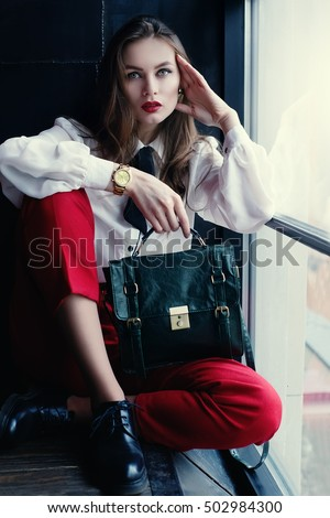 Indoor full body portrait of young fashionable woman posing in loft interior. Model looking at camera.  Lady wearing stylish clothes and holding green handbag. Female fashion concept. City lifestyle.
