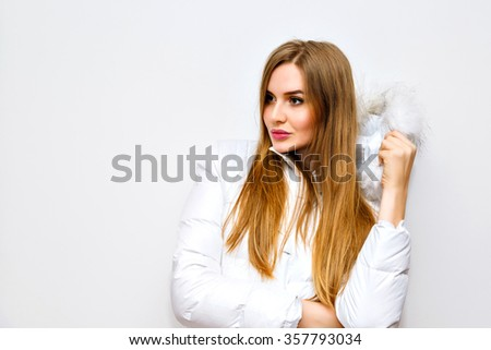 Indoor lifestyle fashion portrait of young blonde woman wearing white winter parka, image with flash, long hairs, natural ,make up, joy, fun. - stock photo