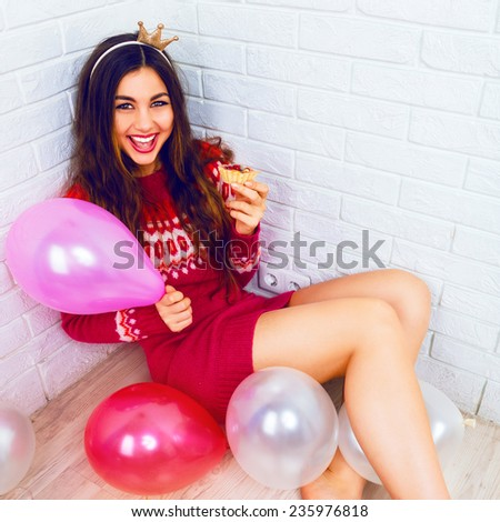 Indoor lifestyle image go pretty young girl sitting on the floor with balloons and celebrating birthday party, wearing casual sweater, screaming having fun, and holding tasty fruit cake. - stock photo