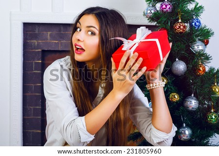 Indoor lifestyle portrait of pretty smiling girl with bright make up and amazing brunette long hairs opening holiday presents from family. Posing near New Year tree and fireplace. Surprised emotions. - stock photo