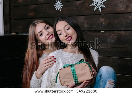 Indoor lifestyle portrait of two pretty young funny girls friends hugs smiling - stock photo