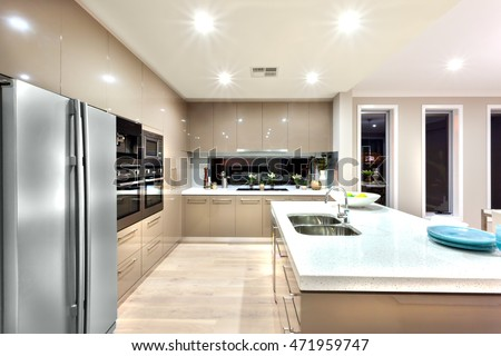 Indoor of the luxury kitchen includes a fridge and wall ovens with cabinets around the kitchen. The counter top made in ceramic has a silver sink and tap. There is a fruit with a white plate