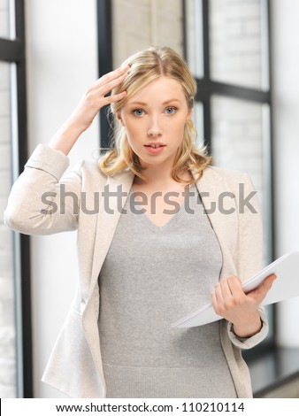 indoor picture of worried woman with documents - stock photo