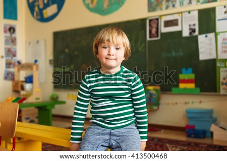 Indoor portrait of a cute little boy in a classroom - stock photo