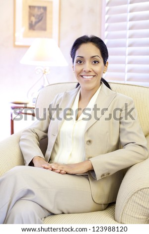Indoor portrait of a young professional attractive Hispanic woman sitting in a comfortable chair
