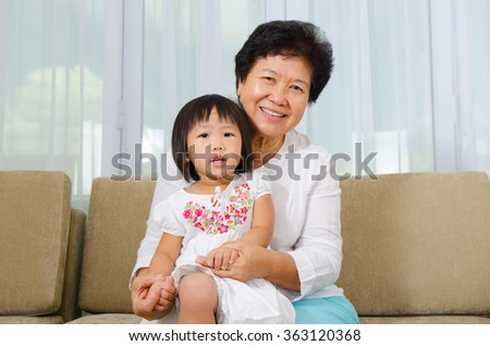 Indoor portrait of asian senior woman and granddaughter - stock photo