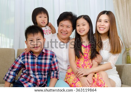 Indoor portrait of asian senior woman together with daughter and grandchildren - stock photo