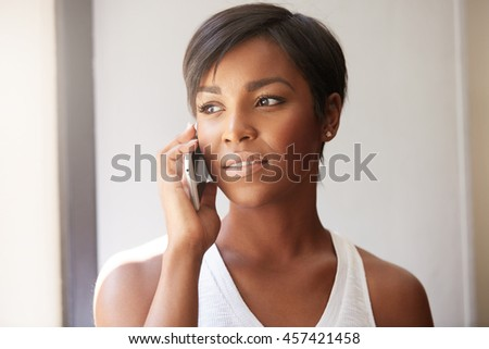 Indoor portrait of attractive young dark skinned African woman, using cell phone for ordering pizza for dinner, looking interested, smiling, looking through the window. Female having a phone talk - stock photo