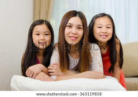 Indoor portrait of beautiful asian mother and daughters lying on sofa - stock photo