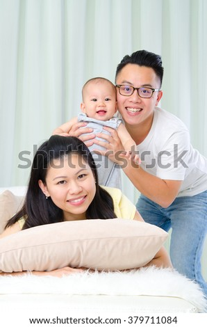 Indoor portrait of cheerful asian family - stock photo