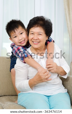 Indoor portrait of cheerful asian senior woman and grandson - stock photo