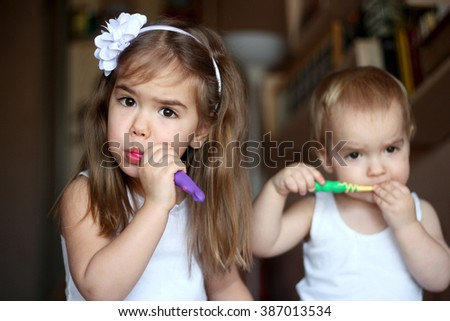 Indoor portrait of cute little kids brushing their teeth, focus on the girl, her brother is on the background, happy family and dental hygiene - stock photo