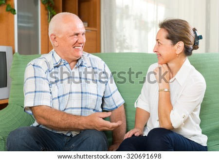 Indoor portrait of loving senior couple talking together in home interior. Focus on man  - stock photo