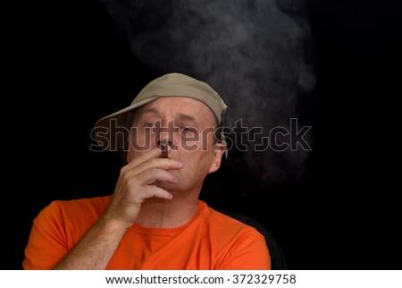 indoor portrait of mature man wearing baseball cap and smoking cigar - stock photo