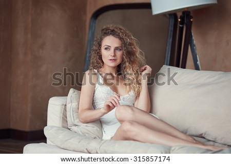 Indoor portrait of young blond sexy woman in sleepwear