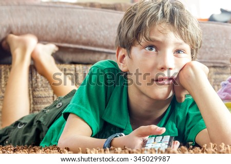 indoor portrait of young boy watching tv at home