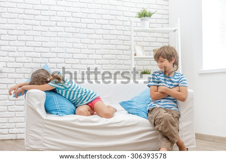 indoor portrait of young children, kids, boy and girls, sitting on sofa at home - stock photo