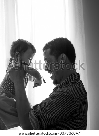 Indoor portrait of young father hugging his little daughter in black and white image. Selective Focus, High Contrast. High Key on the Background
