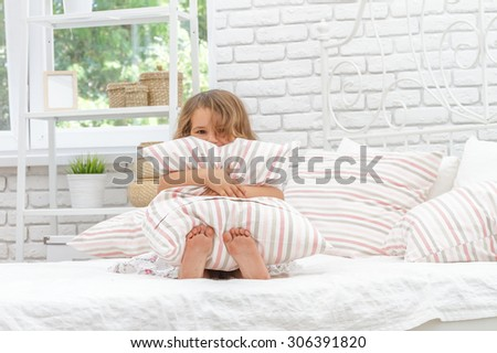 indoor portrait of young happy smiing child girl in her bed, happy morning time - stock photo