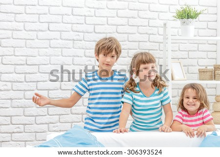 indoor portrait of young happy smiing children, kids, boy and girls, hiding behind sofa at home - stock photo