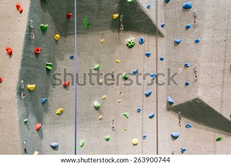 Indoor rock climbing wall in a sport facility where many practice to be fit and in better health - stock photo