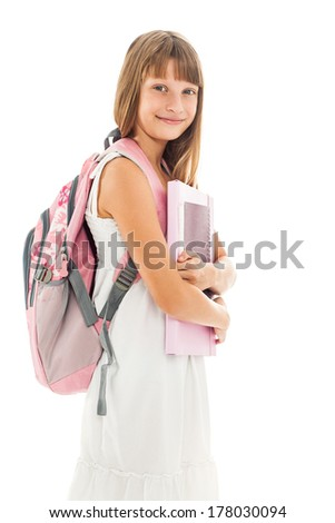Indoor shot of a cute smiling schoolgirl holding her books. - stock photo