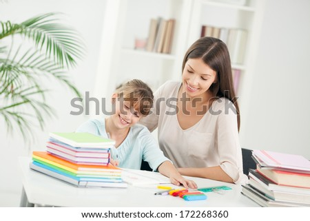 Indoor shot of a smiling mother helping her daughter with the homework.