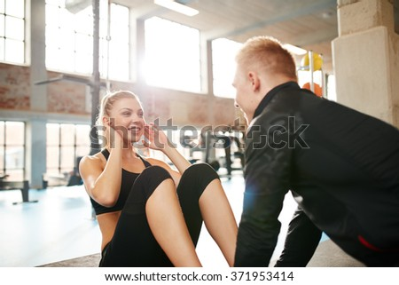 Indoor shot of a young woman doing sit-ups while a personal trainer holding her feet. Happy female  doing abs exercise with help from a man in gym. - stock photo